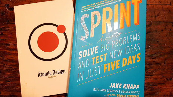 A photograph of Atomic Design and Sprint books on a wooden table